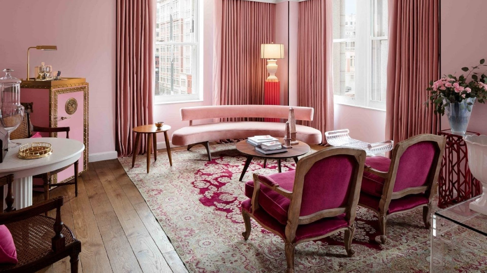 A Living Room Filled With Furniture And A Pink Chair